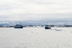Ship sailing between icebergs in the arctic sea in Svalbard Stock Photo