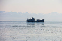 The ship, sailing on Lake Baikal Sayan Mountains in the background. Stock Images