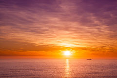 Ship sailing in the ocean at orange sunset Stock Image