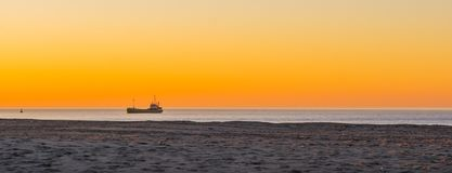 Ship sailing in the ocean at sunset, colorful orange sky, nature and transport background. A ship sailing in the ocean at sunset, colorful orange sky, nature and royalty free stock images