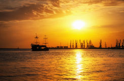 Ship sailing on the sea to the shore at sunrise. Royalty Free Stock Images