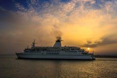 Ship sailing at sunset Stock Photo