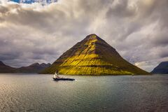 Ship sails along the island of Kunoy in the Faroe Islands, Denmark