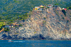 Ship sails in front of the cliff where stands Corniglia, 5 Terre Royalty Free Stock Photos