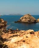A ship sails between the rocks in the bay near Ibiza stock photos