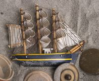 Ship and sails in the sand. A small ship with sails laying in the sand Royalty Free Stock Image