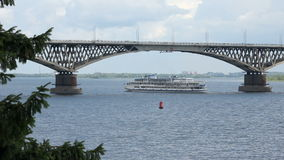 The ship sails under the bridge Saratov-Engels, Volga river, Russia.  stock footage