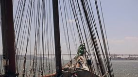 Ship sails through the waves on a bridge background Lisbon stock video