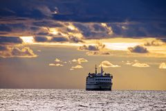 Ship on sea. Cruise ship on the restless sea under stormy clouds during sunset Royalty Free Stock Photos