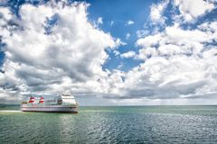 Ship in sea on cloudy blue sky. Seascape with ocean liner and clouds. Summer vacation, adventure and wanderlust concept. Water tra Stock Image