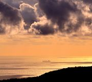 Ship on the sea at dawn. Clouds and ship on the sea at dawn Royalty Free Stock Photo