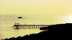 Ship is at sea at dawn, near the beach, long shot stock footage