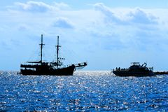 Ship in the sea, sun glare on the water, the sky, the silhouette. The two ships met in the sea a bright Sunny day on backlighting stock photo