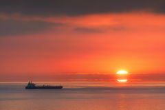 Ship on the sea at sunset Stock Image
