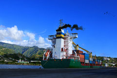 Container Ship in Port. Container Ship in Papeete, tahiti port with steam coming out in good weather blue sky stock photography