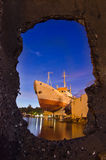 Ship on shore in night harbor - stone frame Stock Image
