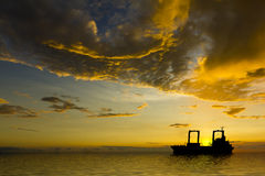 Ship Silhouette with Stormy Clouds at Sunset. Clouds and sunset photograph, ship is graphic and ocean CGI Royalty Free Stock Image