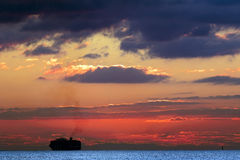 Ship silhouetted on the horizon. A container ship entering Marsaxlokk Harbor Malta, to un/load its containers at the Malta Freeport early in the morning with the Royalty Free Stock Photo