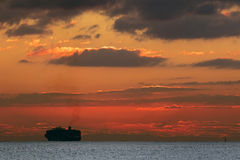 Ship silhouetted on the horizon Royalty Free Stock Photo