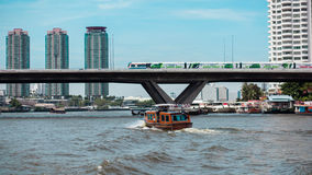 Ship and sky train. Boats on the river and the train tracks and buildings in the city center of Thailand Stock Photo