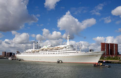 Ship SS Rotterdam. The famous white ship SS Rotterdam on the river Rotte with cloudly blue sky and buildings on the background Royalty Free Stock Photo
