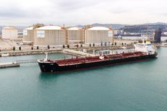 Ship and storage tanks. Barcelona, Spain - September 7th 2015: A ship unloading its cargo into storage tanks. The port is an important commercial area stock photos
