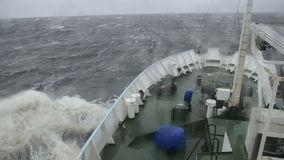 The ship is in a storm at sea. Big wave hits the bow of a ship in a storm