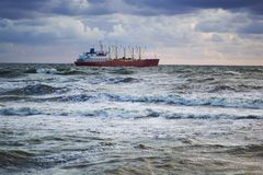 Ship in stormy sea. General purpose vessel heading through the storm to the open sea Royalty Free Stock Photo