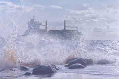 Ship in a stormy sea. Silhouette of a commercial ship in a stormy Baltic sea through the spray of the waves on the rocks on the shore stock photo