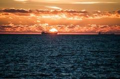 Ship on sunrise sea stock photos