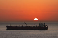Ship at sunset. Cargo freight rig ship silhouette at sunset with sun on horizon.  Logistics concept Royalty Free Stock Photo