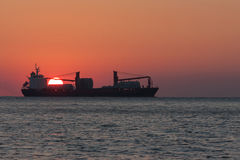 Ship on sunset background. Silhouette of a ship on a red sunset background stock image