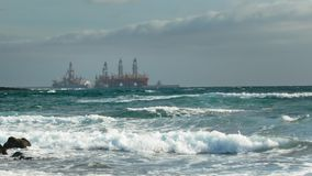 Ship tanker near oil rigs in the ocean offshore. Stormy sea, waves and foam. Concept of oil extraction from the ocean