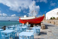 Ship and tavern furniture on quay in Mykonos, Greece. Red boat and blue tables on sea beach. Beach restaurant with sea. View. Summer vacation on mediterranean Royalty Free Stock Photography