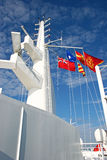 Ship Tower with Flags. The main tower on a cruise ship holds radar equipment and flies colorful flags Royalty Free Stock Photos