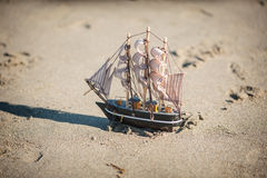 Ship is a toy in the sand Stock Images
