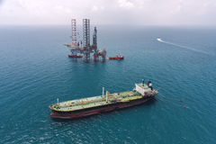 The ship transporting. The oil and an oil rig off-shore drilling platform Stock Photos