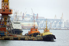 Ship and tug-boat in harbor Stock Photos