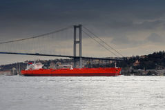 Ship under bosphorus bridge. Before the storm,istanbul in turkey.bosporus form a border betwesn asia and europe Royalty Free Stock Images