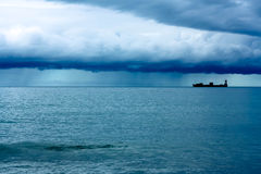 Ship under Rain Clouds Stock Photography