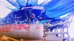 Ship repair. Ship under repair and sandblasting, painting in floating dock of shipyard Royalty Free Stock Photo