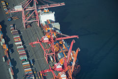 Ship Unloading at Dock. Aerial perspective of a freight ship unloading containers in Seattle Stock Image