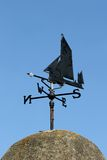 Ship Weather Vane. Old black wrought iron weather vane of a ship design pointing west, set against a blue sky stock images