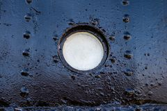 Ship window. A small ship window of a large merchant ship standi. Ng in the port. Season of the early spring Royalty Free Stock Image