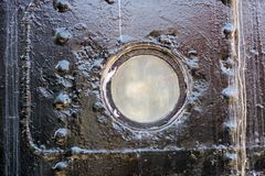 Ship window. A small ship window of a large merchant ship standi. Ng in the port. Season of the early spring Royalty Free Stock Photography