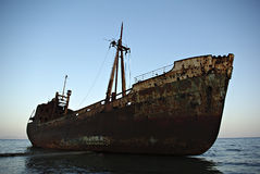 Ship Wreck. Old rusty abandoned ruined vessel, stranded in shallow water of sandy beach Stock Photography