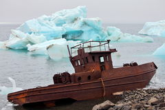 Ship wreck on Arctic coast with icebergs on background Stock Photos