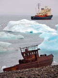 Ship wreck on Arctic coast with icebergs and icebreaker Stock Images