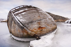 Ship-wreck in ice. An old wooden ship halfway sunken in an ice covered archipelago Stock Photo