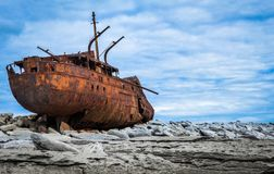 Ship wreck on rocks Aran island. Ship wreck rust, white rocks and blue cloudy sky on background. This ship has been transported by a storm far on shore Royalty Free Stock Photography